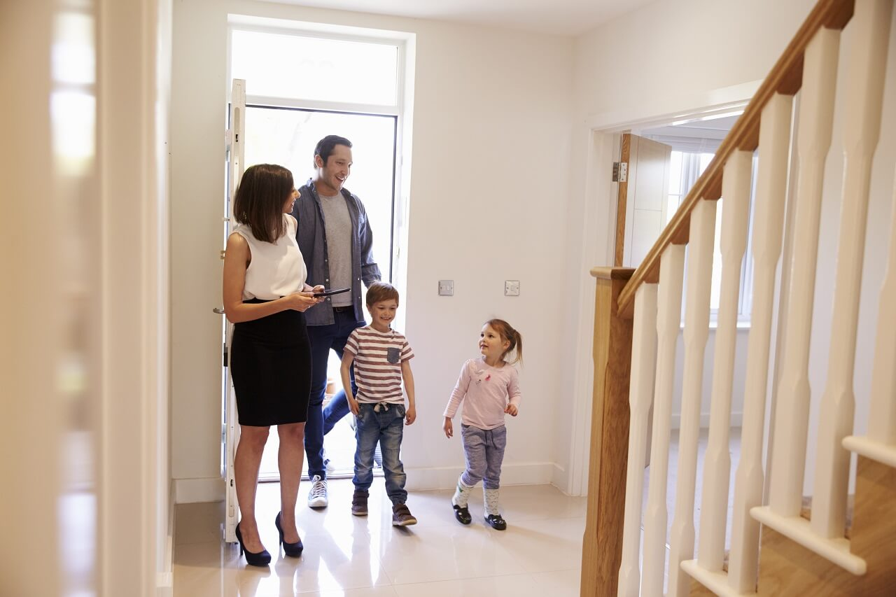 realtor showing young couple with kids homes for sale