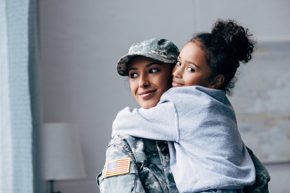 military woman hugging daughter - homes for sale in fort carson colorado